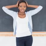 Black woman upset next to a blackboard in a classroom